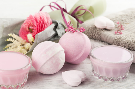 SPA composition with pink bath bombs, rununculus, heart on white wooden background. Top view, copy space