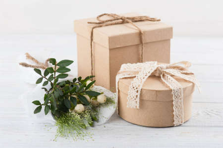 Rustic craft gift boxes with wild, flowers, leafs, twigss on wooden background. Concept for workshop or celebration. Shabby chic style