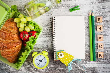 Green lunch box with croissant, salad, tomato, grape. On wooden background, empty notebook