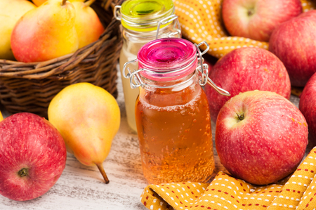 Homemade apple and pear cider and fresh fruits on wooden table