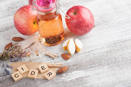 Homemade apple cider and fresh apples on a wooden table background