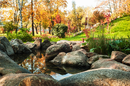 Autumn scenery of park in japanese style with red bridge, stone garden with zen atmosphere
