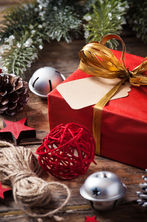 Red christmas present with golden bow on dark wooden background in vintage style Stock Photo