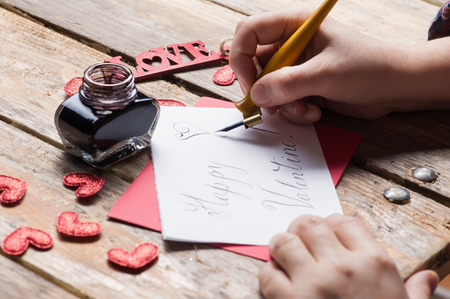Female hands hand lettering Happy Valentine sign, DIY composition on rustic wooden table. Calligraphy concept 免版税图像