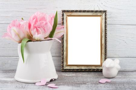 Fresh pink tulip flowers in jug, empty photo frame on rustic wooden background Banco de Imagens