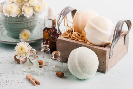 Spa products with bath bombs, essential oil and dry herbs in small bottles on light blue background. Alternative treatment concept in provence style