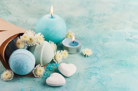 Spa products with bath bombs, sea salt and flowers on blue background. Beauty treatment concept with lit aroma candle