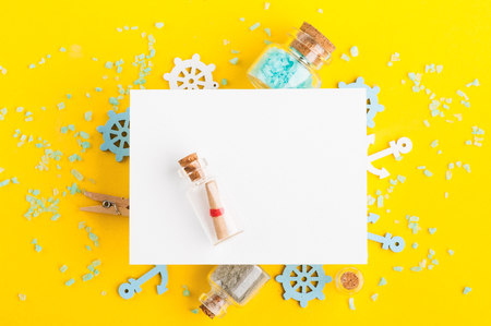 Bright summer holidays background with blank card, sea salts, nautical decor on yellow desk top view