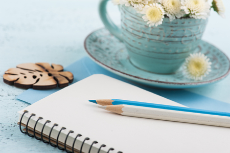 Empty notepad with white chrysanthemum flowers in cup on blue wooden background