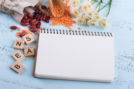 Blank note pad, kidney beans and red lentils on blue wooden background