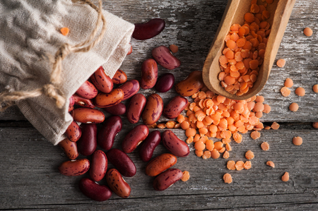 Kidney beans and red lentils on old wooden background