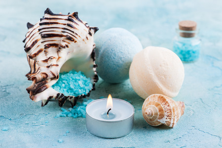 Spa products with sea shells and salt on blue background. Beauty treatment concept