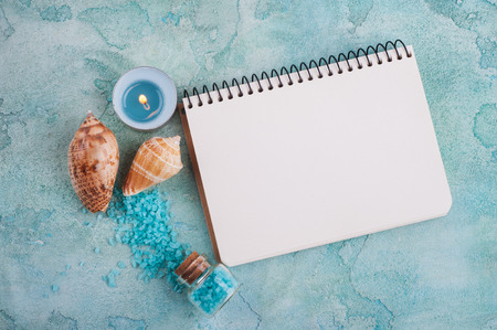 Empty note book top view and Spa products with sea shells and salt on blue background. Beauty treatment concept Banco de Imagens