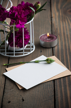 Bunch of purple carnations, blank card and lit candles on rustic vintage wooden background with copy space Banco de Imagens