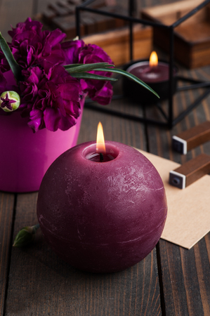 Bunch of purple carnations on rustic vintage wooden background with lit candle