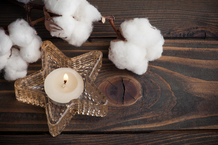 Star shape candle and cotton flowers on old wooden background Standard-Bild - 121739218