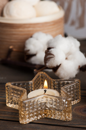 Spa products with golden candle and cotton flowers Standard-Bild - 121739239