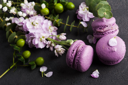 Purple macarons and flowers on concrete background. French dessert with fresh flowers 免版税图像