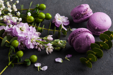 Purple macarons and flowers on concrete background. French dessert with fresh flowers Banco de Imagens