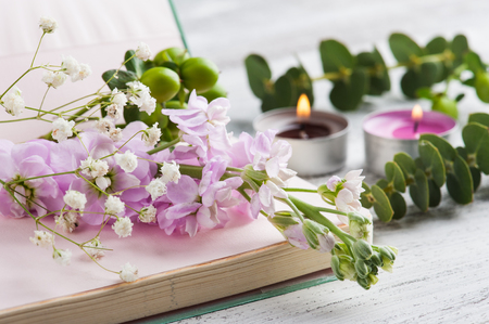 Open notepad with flowers and candles on rustic white wooden table. Still life closeup