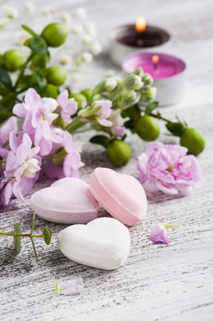 Spa products with bath bombs and candles. Green flowers on background