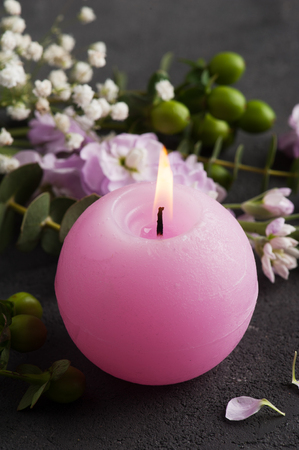 Flowers and lit candle on rustic concrete background. Still life with copy space for text