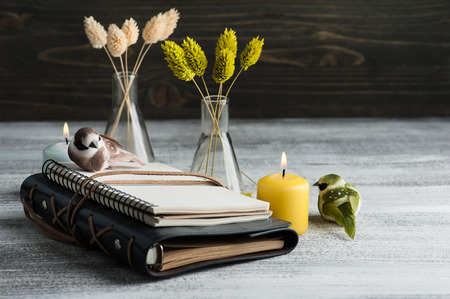Blank empty open notebook on old wooden table. Lit candles and dry flowers as decoration Banco de Imagens