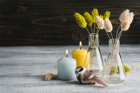 Lit candles and dry flowers as decoration in rustic interior