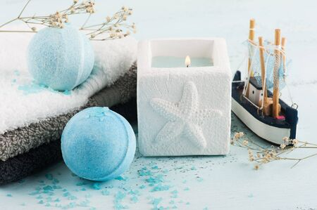 Spa set with blue bath bombs, towels and lit candle