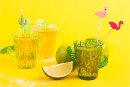 Shot of tequila in cactus glass with limes on bright yellow background 스톡 콘텐츠
