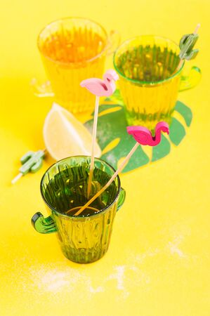 Shot of tequila in cactus glass with limes on bright yellow background< copy space
