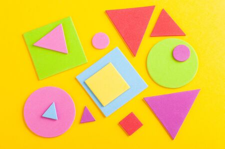 Abstract bright background of colorful geometric figures, cut from paper on yellow