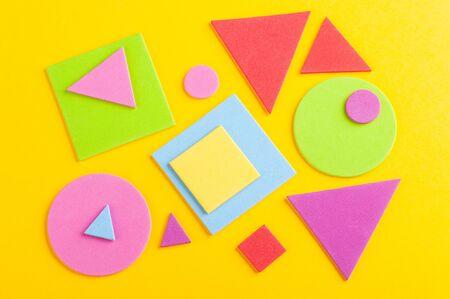 Abstrakter heller Hintergrund aus bunten geometrischen Figuren, aus Papier auf Gelb geschnitten