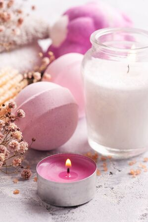 Pink aroma bath bombs in SPA arrengement with dry flowers and lit candle