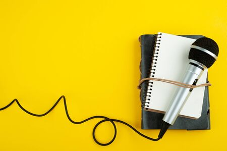 Microphone and empty open note book on yellow paper background. Copy space for your text. Blog, potcast concept