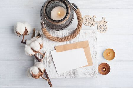 Empty note and kraft envelope on shabby chic wooden background. Copy space for text and lit candles Stock fotó