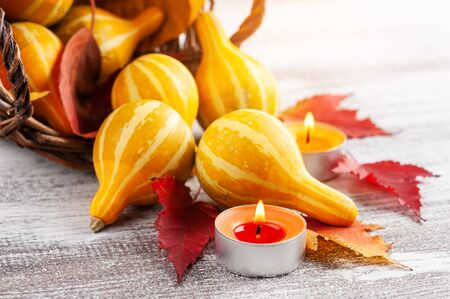 Small decorative pumpkins  with lit candles and falling leaves on rustic wooden table. Thanksgiving or halloween set with copy space Фото со стока