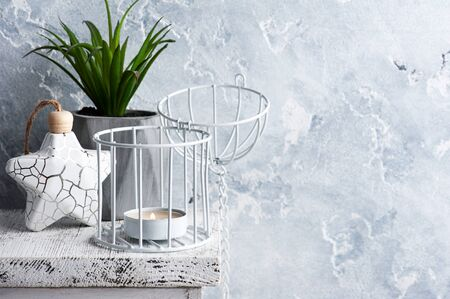 Scandinavian interior with lit candle and succulent as decor on concrete background. Copy space for text