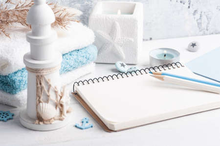 Empty notebook with blue nautical decor and lit candle as decoration. Holiday or wedding planner concept with pencils