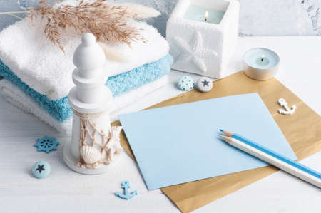 Empty envelope with blue decor and lit candle as decoration. Holiday or wedding planner concept with pencils Archivio Fotografico
