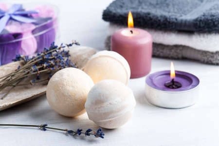 Vanilla aroma bath bombs in spa composition with dry lavender flowers and towels. Aromatherapy arrangement, zen still life with lit candles