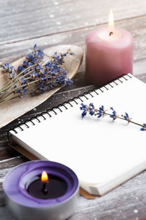 Blank note book, purple aroma candles and dry lavender flowers on wooden rustic background. Summer or autumn set with copy space