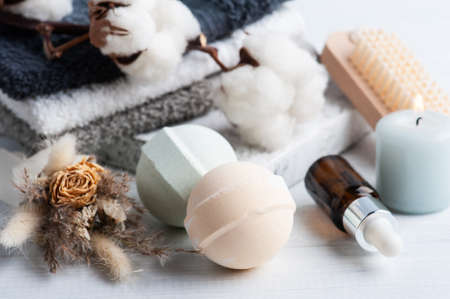 Oil bottle and aroma bath bombs in spa composition with dry flowers and towels. Aromatherapy arrangement, zen still life with green lit candles and body brushes