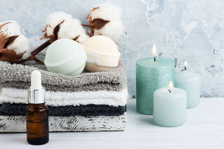 Green aroma bath bombs in spa composition with dry flowers and towels. Aromatherapy arrangement, zen still life with lit candles and body brushes