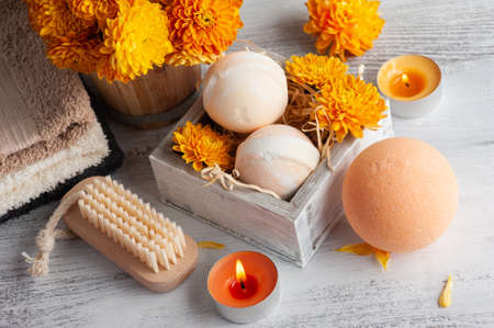 Aroma bath bombs in spa composition with orange flowers and towels. Aromatherapy arrangement, zen still life with lit candles