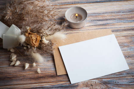 Blank note and lit aroma candle and dry flowers on rustic background. Greeting card for wedding
