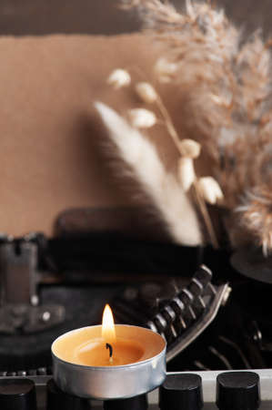 Typewriter close up and dry flowers with lit aroma candle. Valentines concept, vintage toned and kraft paper 免版税图像
