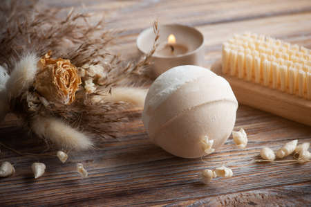 Vanilla peach aroma bath bombs in spa composition with dry flowers. Aromatherapy arrangement, zen still life with lit candles and body brushes 免版税图像