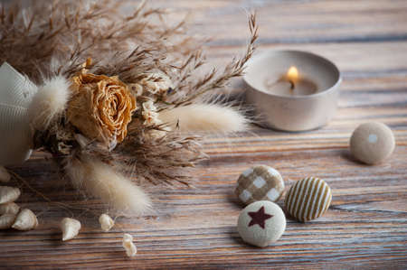 Lit aroma candle and dry flowers on rustic background. Greeting card for wedding