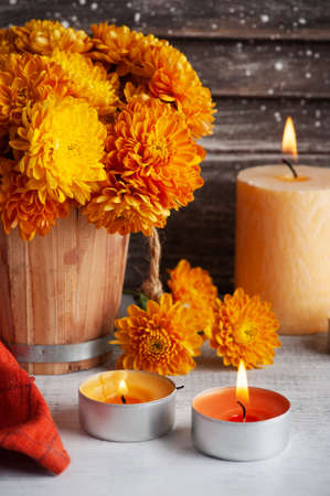 Lit aroma candles and orange flowers on rustic background. Greeting card with copy space for your text